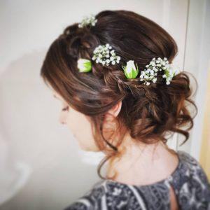 vlecht en bloemen laag opgestoken bruidskapsel